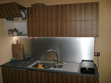 cucina su misura in legno marrone con forno nero