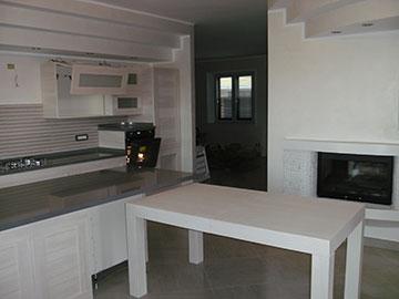 cucina moderna con tavolo bianco e penisola