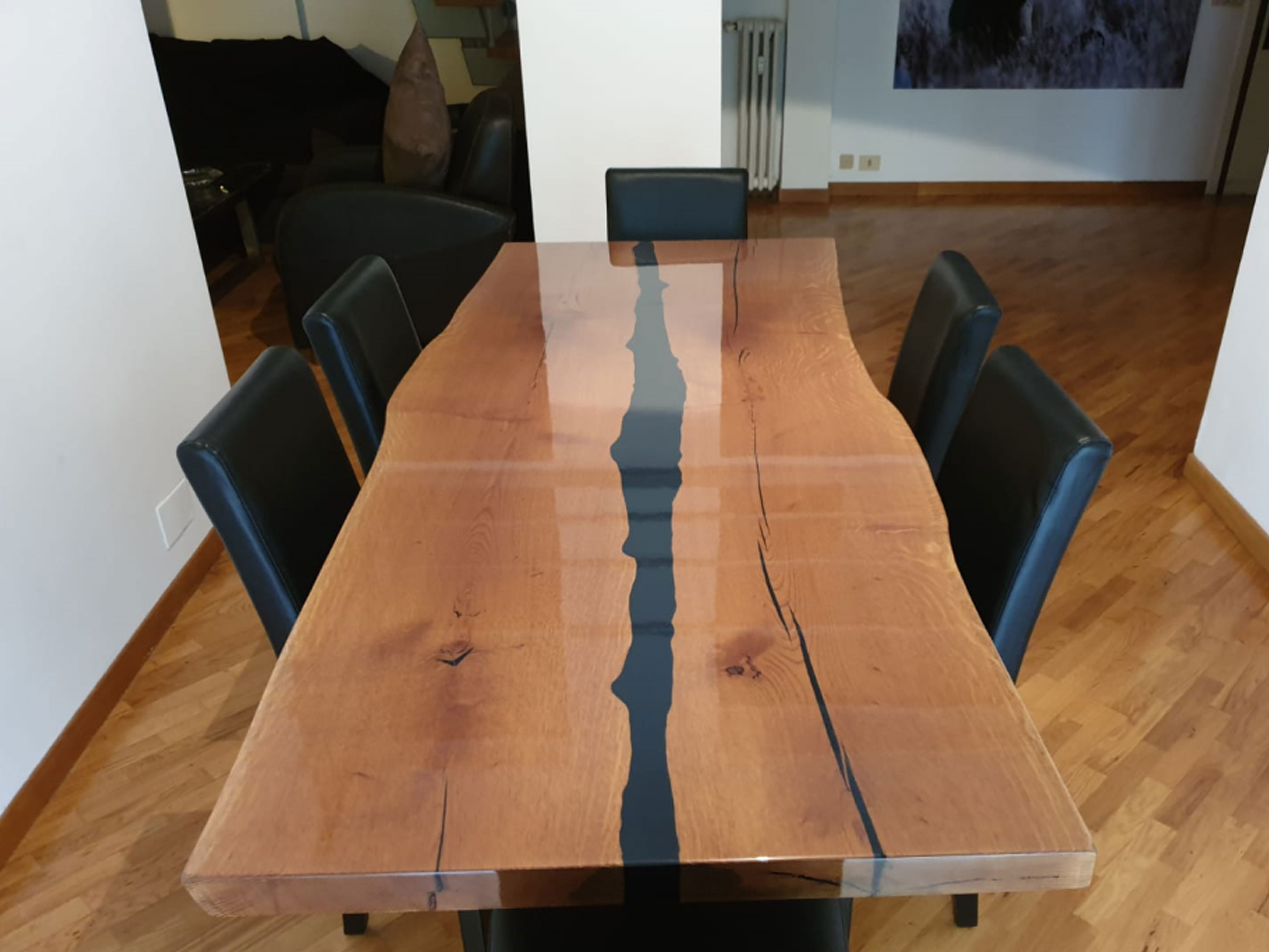tavolo con piano in legno naturale e venature nere a vista