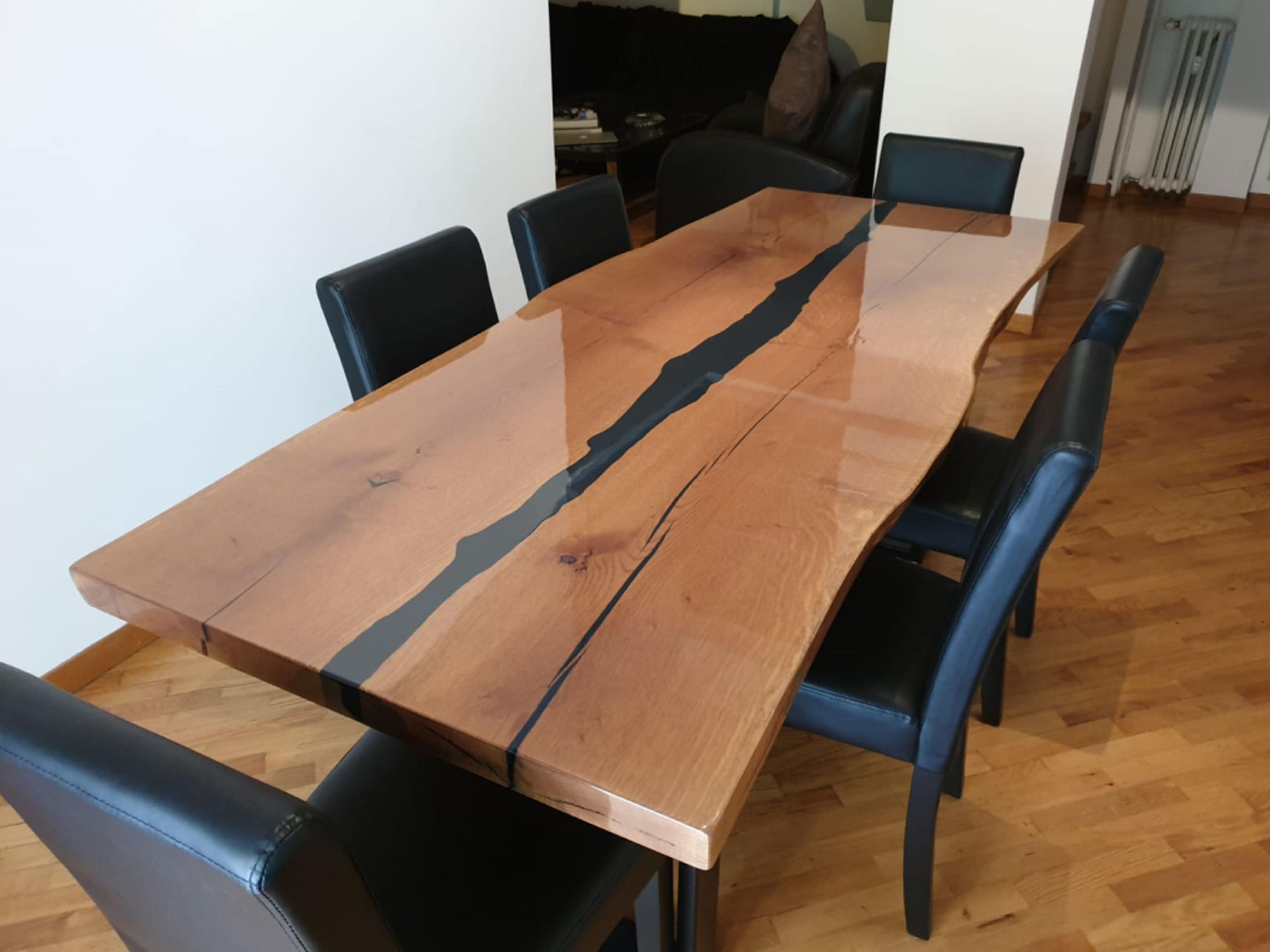 tavolo con piano in legno naturale e venature nere e sedie nere in pelle